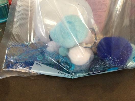 blue baby oil glitter sensory mat pompoms rubber bands beads foodsaver sealed giant google eyes